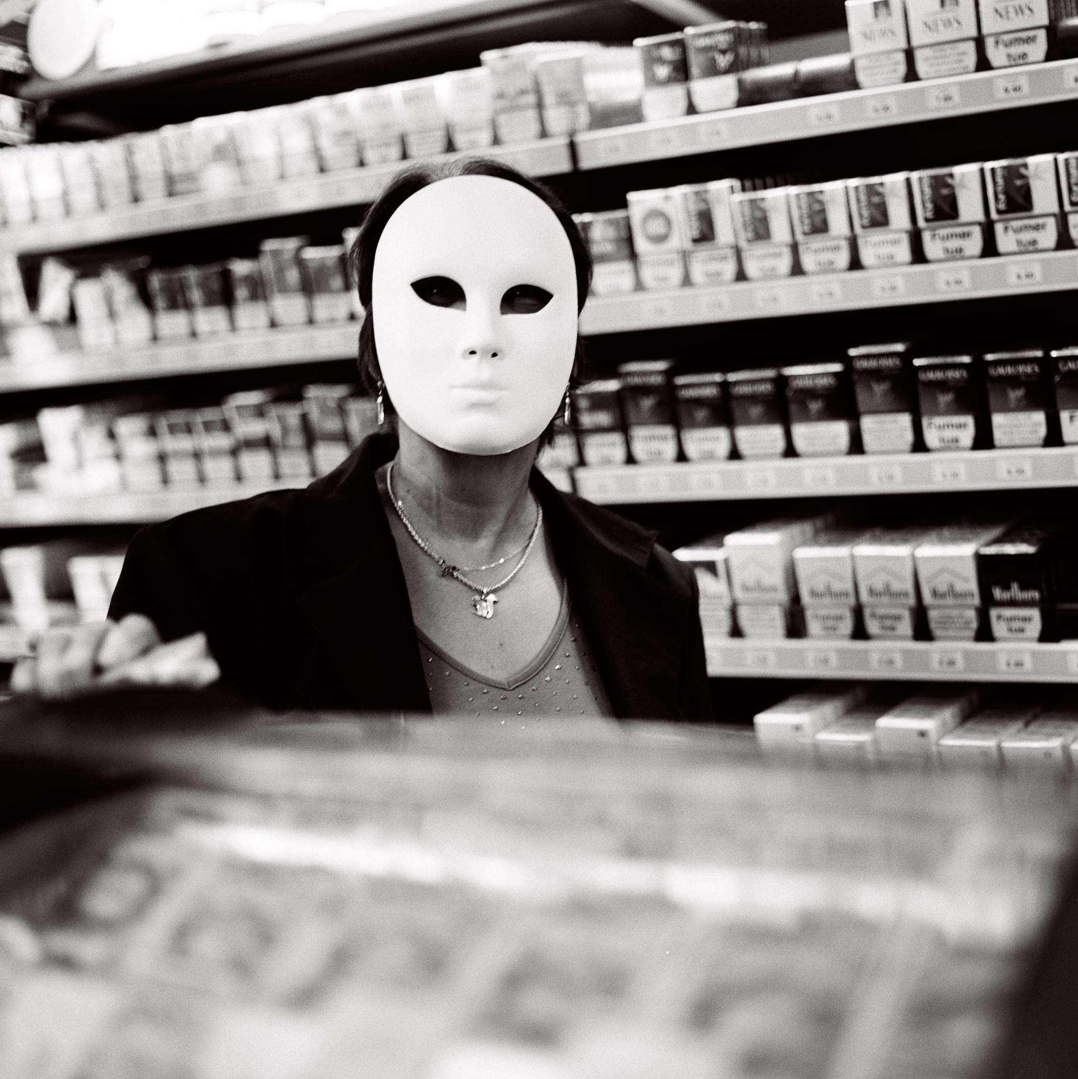 photographie d'art d'une buraliste portant un masque